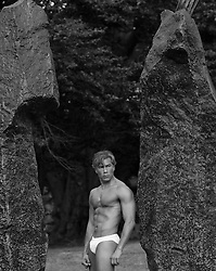 sexy Asian American man in white briefs standing by large rocks outdoors