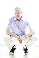caucasian senior man portrait squatting cheerful isolated studio on white background