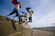Four children leap out into the wide blue yonder on a beach in Whitley Bay, England. Jumping at a height from a sea defence wall, the kids all hold their towels above their heads and as they leave the ground, look down to their landing spot - the soft sand below. It is a scene of chilhood recklnessness, when children and young people take risks that adults don't. But  youngsters don't have a sense of danger but instead, exhilarating desire for adventure. The beach in the distance is largely deserted so the kids have lots of space to fulfill their games.