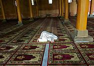 A solitary woman praying facing Mecca in the Jamia Masjid.