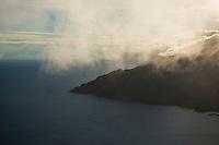 Low clouds conceal view over coastline from mountain peak, Lofoten Islands, Norway