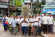 29 JUNE 2014 - DAN SAI, LOEI, THAILAND:  People in a merit making procession walk through Dan Sai on the their way to Wat Ponchai on the last day of the Ghost Festival. Phi Ta Khon (also spelled Pee Ta Khon) is the Ghost Festival. Over three days, the town's residents invite protection from Phra U-pakut, the spirit that lives in the Mun River, which runs through Dan Sai. People in the town and surrounding villages wear costumes made of patchwork and ornate masks and are thought be ghosts who were awoken from the dead when Vessantra Jataka (one of the Buddhas) came out of the forest. On the last day of the festival people participate in merit making ceremonies at the Wat Ponchai in Dan Sai and lead processions through town soliciting donations for the temple.   PHOTO BY JACK KURTZ