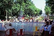 People sitting around water fountain and boating pond, Aix-les-Bains, Savoie, France, 1974