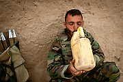 An Afghan National Army soldier drinks water from a plastic jug after a firefight.