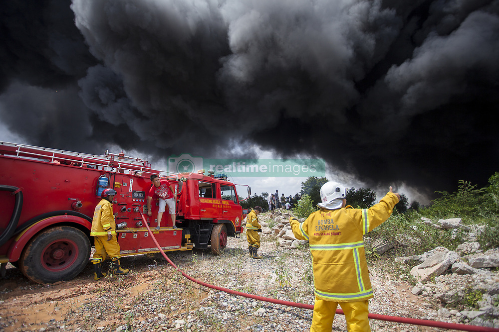 June 16, 2018 - Sungai Petani, Kedah, Malaysia - Kota Sarang Semut Volunteer Fire Brigade arrived at the fire scene and quickly disperse to control the fire involving three factories in Sungai Petani. The fire broke at 1:00 PM and razed a plastic recycling centre, a plywood processing factory and a casket factory. Fire fighters were having a hard time to control the fire due to wind condition and flammable products. (Credit Image: © Aizzat Nordin/SOPA Images via ZUMA Wire)