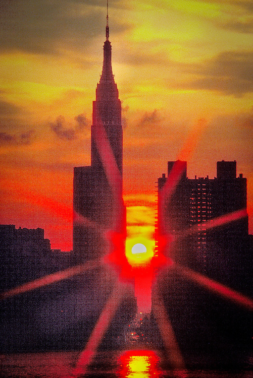 A fiery sun sets behind the Empire State Building and New York's 34th Street circa 1985, as seen from across the East River.
