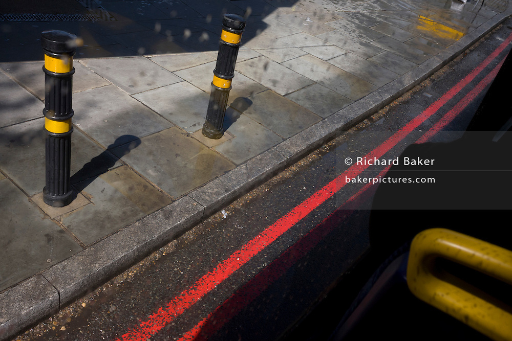 Traffic bollards and red route stripes outside of a London bus window.