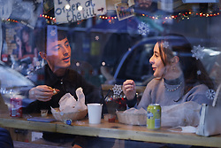© Licensed to London News Pictures. 15/12/2020. London, UK. A couple enjoy a meal in a cafe in Soho, central London. London and other areas of the south east are to enter tier three restrictions at midnight tonight as Covid-19 infection rates rise. Photo credit: Peter Macdiarmid/LNP
