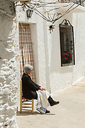 Senior woman sitting outdoors on chair, Pampaneira, Andalusia, Spain