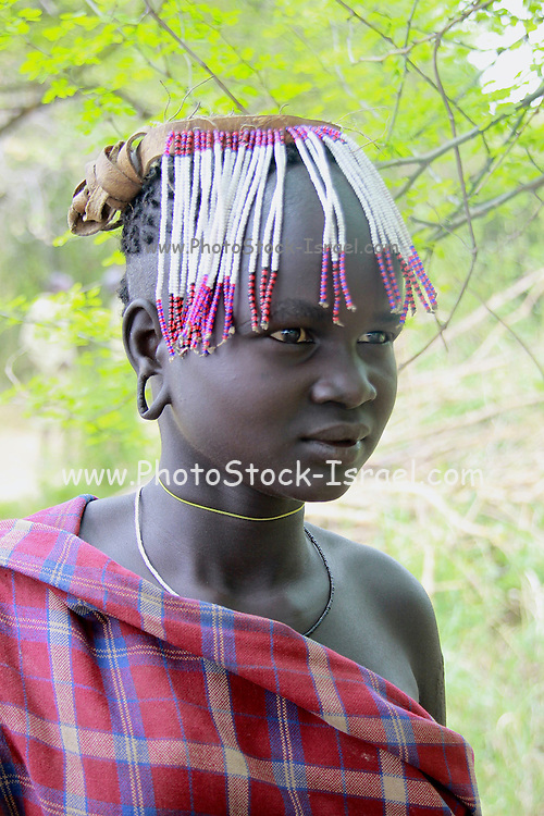 Africa, Ethiopia, Debub Omo Zone, Mursi tribesmen. A nomadic cattle herder ethnic group located in Southern Ethiopia, close to the Sudanese border. a young girl with elongated ear lobes decoration