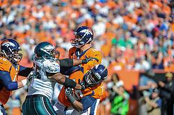 Sep 29, 2013; Denver, CO, USA; Philadelphia Eagles linebacker Brandon Graham (55) battles Denver Broncos tackle Chris Clark (75) and applies pressure to Denver Broncos quarterback Peyton Manning (18) during the game at Sports Authority Field at Mile High. Mandatory Credit: John Geliebter-Philadelphia Eagles
