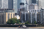 Two river workmen wearing high-vis clothing stand at the stern of their Port Of London Authority boat beneath Thames riverside residential and office properties at Canary Wharf in London Docklands, on 16th September 2021, in London, England. Canary Wharf was once a thriving Victorian cargo dock but after Thames shipping declined from the 1960s, its derelict areas were redeveloped in the 19080 by Margaret Thatchers Docklands Development Corporation created one of the UK's main financial centres, now home to the European Headquarters of numerous major banks including Barclays, Credit Suisse and HSBC.