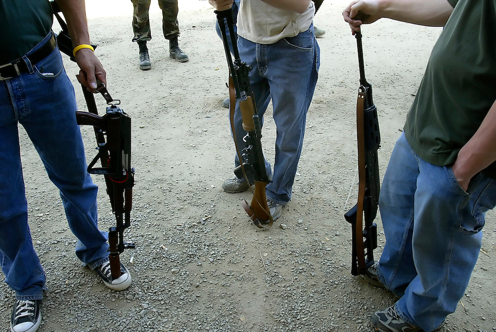 Men with automatic weapons for sale stand around offering their wares during the Knob Creek Machine Gun Shoot near West Point, Kentucky April 10, 2005. Thousands of machine gun and military hardware enthusiasts attended the event held each year over weekends in the spring and fall.