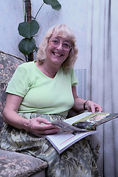 Portrait of an older woman sitting on the sofa reading,
