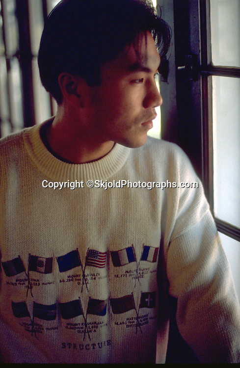 Korean American college student age 21 thoughtfully looking out window.  St Paul  Minnesota USA