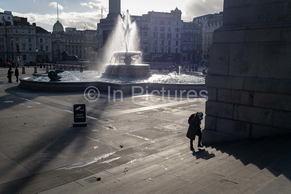 With one of the famous fountains at the base of Nelson's Column behind, a solitary person walks through Trafalgar Square and up the steps on 12th November 2020, in London, England.
