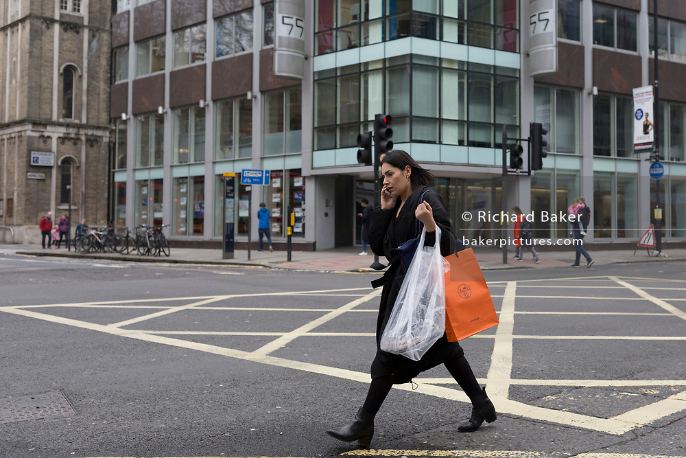 The day after Facebook's Mark Zuckerberg faced Senate Committee questions in Washington, a lady uses her mobile phone outside the offices of Cambridge Analytica on New Oxford Street, the UK company accused of harvesting the personal details of Facebook users (including Zuckerberg himself) in its data privacy scandal, on 11th April, 2018, in London, England.