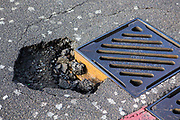 A large road pot hole on the edge of a drainage grate in Hackney, London, United Kingdom.  The responsibility for maintaining safe road surfaces lies with the local authorities, such as Hackney Council.