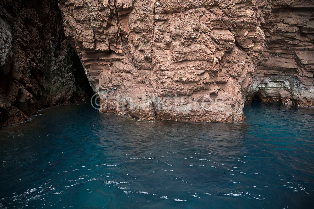 Volcanic cave coastal landscape of the Scandola Nature Reserve on 15th September 2017 in Corsica, France. The Scandola Nature Reserve is located on the west coast of the Corsica, within the Corsica Regional Park. The reserve was established in 1975 and has been recognized by the United Nations as a Natural World Heritage Site, and was inscribed on the World Heritage List in 1983.