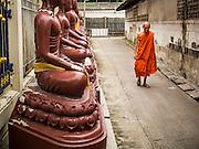 30 AUGUST 2014 - BANGKOK, THAILAND:     A Buddhist monk walks past a row of Buddha statues near Wat Chimthayakawat in the Thonburi section of Bangkok.  PHOTO BY JACK KURTZ