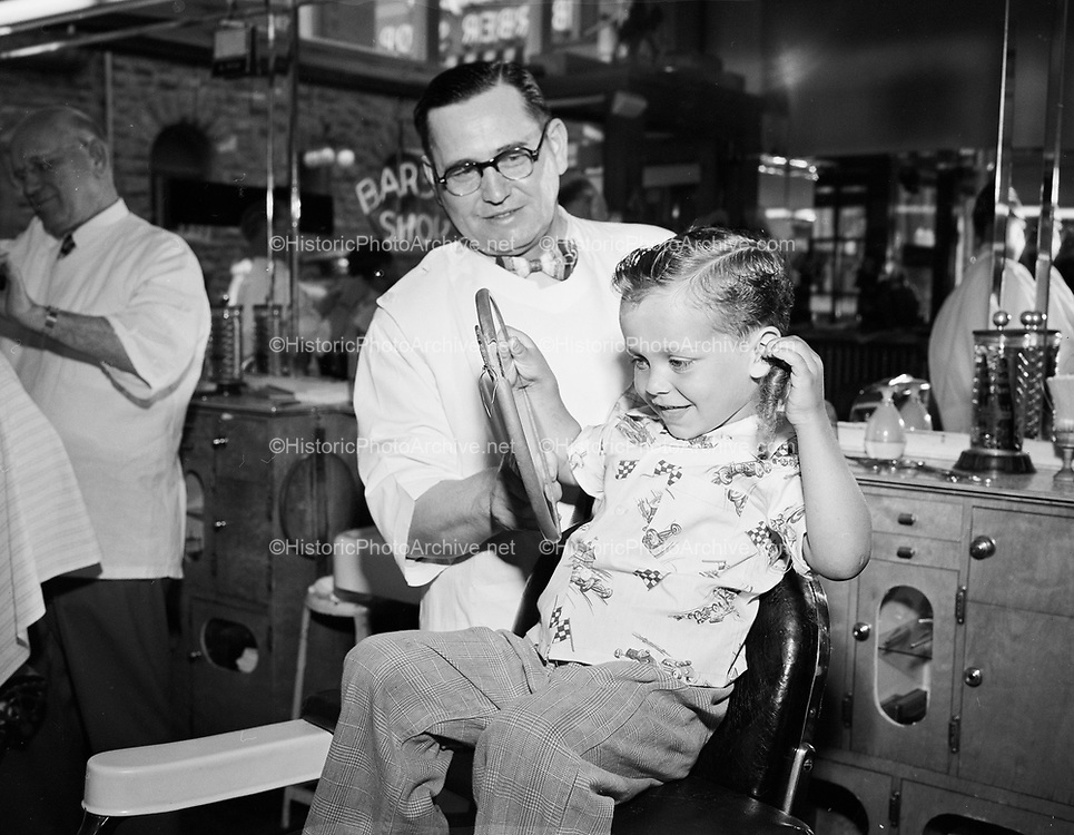 Y-500526. Barber shop. Barber Albert Sutko, owner of the Antiseptic Barber Shop, 622 SW Yamhill, Portland, is giving a haircut to a young man. In the background through the window and across the street is the old Portland Hotel. May 26, 1950.