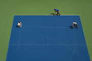 8/07/2012 9:58:16 AM -- Flushing Meadows, NY, U.S.A<br /> Foreman Cesare Iori, left, and worker Hector Ayala, right, use a long piece of string as a snap line as Oscar Romero, center, applies tape to the court's surface before painting its lines in Arthur Ashe Stadium. The chalk line will serve as a guide for the painters.  Each court at the USTA Billie Jean King National Tennis Center gets 11 applications of resurfacing material, with each application containing a different formula of rubber, acrylic, and silica.  The rubber gives the surface a cushion, and the silica gives it texture, which affects the speed of the ball as it comes off the court.  Photo by Emile Wamsteker, Freelance