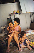 POOR SINGLE MOTHER. Rocinha Favela, Rio de Janeiro, Brazil, South America. Child on Batman bike. in shanty hut. Although Rocinha is technically classified as a neighborhood, many still refer to it as a favela. It developed from a shanty town into an urbanized slum. Today, almost all the houses in Rocinha are made from concrete and brick. Some buildings are three and four stories tall and almost all houses have basic sanitation, plumbing, and electricity. Compared to simple shanty towns or slums, Rocinha has a better developed infrastructure and hundreds of businesses. There is also lots of deliquency, crime and drugs in the favelas.