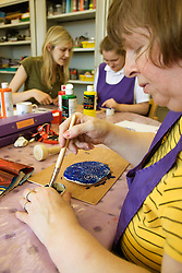 Day Service Assistant working with Day Service users with learning disabilities in an arts and crafts session,