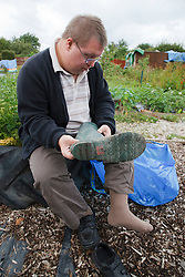 Man with learning disability taking boots off on allotment
