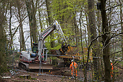 HS2 workers observe a large mechanical digger being used for the translocation of soil in ancient woodland at Jones Hill Wood in the Chilterns AONB on 28th April 2021 in Wendover, United Kingdom. Soil translocation is intended to be an environmental mitigation measure for the HS2 high-speed rail link. Felling of Jones Hill Wood, which contains resting places and/or breeding sites for pipistrelle, barbastelle, noctule, brown long-eared and natterer's bats and is said to have inspired Roald Dahls Fantastic Mr Fox, has recommenced after a High Court judge yesterday refused environmental campaigner Mark Keir permission to apply for judicial review and lifted an injunction on felling for the rail infrastructure project.
