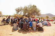 Herero and Himba men in a discussion group at a funeral gathering, Kaokoland, Namibia