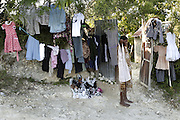 A woman sells clothes in a makeshift store set up outside her home off the dirt road leading up the mountain above Carrefour, Haiti.  Stores, in a typical sense, don't exist and people trade goods.