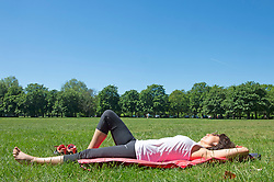 © Licensed to London News Pictures 09/06/2021. Greenwich, UK. A woman sunbathing under a blue sky. Another hot sunny day in Greenwich park, London as temperatures across the UK are forecast to be hotter than Portugal at the weekend. Photo credit:Grant Falvey/LNP