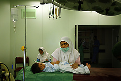Mohammed Yousuf, 4, receives comfort before undergoing surgery for the pelvi-ureteric junction of the kidney inside the Children's Hospital at the Pakistan Institute of Medical Sciences, P.I.M.S., in Islamabad, Pakistan on Sept. 18, 2007.