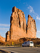 The orange sandstone Courthouse Towers resist erosion in Arches National Park, Utah, USA. These rock monuments are beautiful both at sunrise (seen here) and sunset. The Courthouse Towers are comprised of the Slick Rock member of Entrada Sandstone above the red-brown. or chocolate-brown marker beds of the Dewey .Bridge member. A Volkswagon Eurovan Camper parks at a pullout.