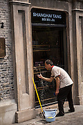 A workers cleans the windows of Shanghai Tang store Xintiandi Plaza shopping district Shanghai, China