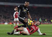 Football - 2017 / 2018 Premier League - Arsenal vs. Manchester United<br /> <br /> Sead Kolasinac (Arsenal FC) slides into Antonio Valencia (Manchester United) as Arsenal pile on the pressure at The Emirates.<br /> <br /> COLORSPORT/DANIEL BEARHAM