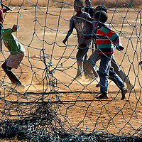 Youngsters kick up the dust as they play soccer in a dirt field at Botshabelo Children's AIDS Village in Magaliesburg, South Africa.<br /> Photo by Shmuel Thaler <br /> shmuel_thaler@yahoo.com www.shmuelthaler.com