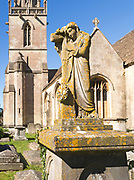 Statue on grave in graveyard of Church of Saint Bartholomew, Corsham, Wiltshire, England, UK