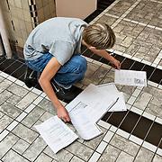Nederland Rotterdam 23-09-2009 20090923 Serie over onderwijs,   openbare scholengemeenschap mavo, havo en vwo.  Jongen neemt lesstof door op de gang tijdens tussenuur, organiseren papierwerk, oefenstof.                                             .Foto: David Rozing