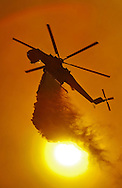 An Erickson S-64 Aircrane drops water over the flames of the Guiberson fire..9000 acre Guiberson wildfire burns out of control near the city of Fillmore, CA. The fire was fed by Santa Ana winds, triple digit temperatures, and single digit humidity levels. Most of the fire burned in rural canyon areas and was started by a manure combustion fire.