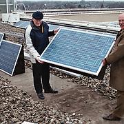Nieuwe zonnepanelen op het dak van het gemeentehuis Huizen door wethouder Kolk