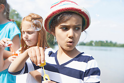 Girls blowing bubbles with bubble wands at lakeshore, Bavaria, Germany