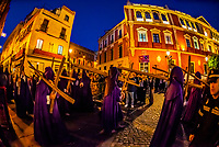 Hooded Penitents (Nazarenos) in the procession of the Brotherhood (Hermandad) La Quinta Angustia carrying crosses, Holy Week (Semana Santa), Seville, Andalusia, Spain.