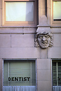 """Humorous photograph of a building wall showing a gargoyle adjacent to a window with the word """"dentist"""" printed on it."""