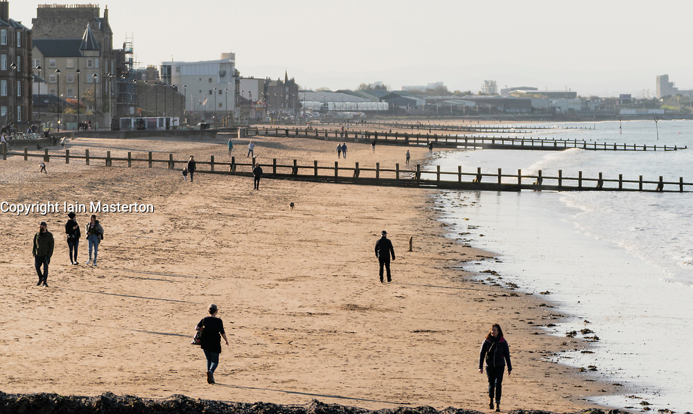 Portobello, Edinburgh, Scotland, UK. 13 April 2020. People outdoors walking and exercising in the late afternoon on Portobello beach. Although the weather was sunny the beach was much quieter than normal and most people were exercising appropriate social distancing.  Iain Masterton/Alamy Live News