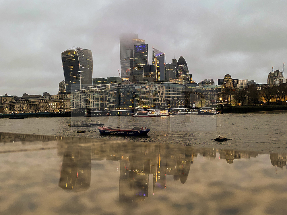 © Licensed to London News Pictures. 13/12/2020. London, UK. Reflection of London's financial district on a wet surface caused by rainfall on a wet day in the capital. Photo credit: Dinendra Haria/LNP