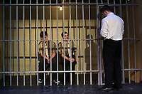 "Jonathan Buttrick PFC Louden Downey and Josh Testa Lance CPL Harold W. Dawson sit in their cell as Lt. Daniel Kaffee steps in for an interrogation during dress rehearsal for ""A Few Good Men"" at Gilford High School Monday afternoon.  (Karen Bobotas/for the Laconia Daily Sun)"