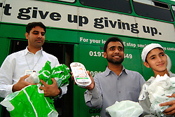 NHS Health Promotion workers hand out dates and stop smoking information at mosque to encourage Muslims to stop smoking during Ramadan; Bradford; Yorkshire UK