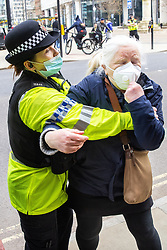 © Licensed to London News Pictures. 07/03/2021. Manchester, UK. Police struggle with then detain a woman , alleging obstruction of police , before forcibly leading and placing her in to a police van . Police break up what they say is an illegal gathering under Coronavirus legislation as nurses and their supporters attempt to protest in St Peter's Square in Manchester City Centre over the British Government proposing a one percent pay increase to nurses' salaries . Photo credit: Joel Goodman/LNP
